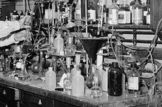 black white photo of beakers and test tubes, arms of a man