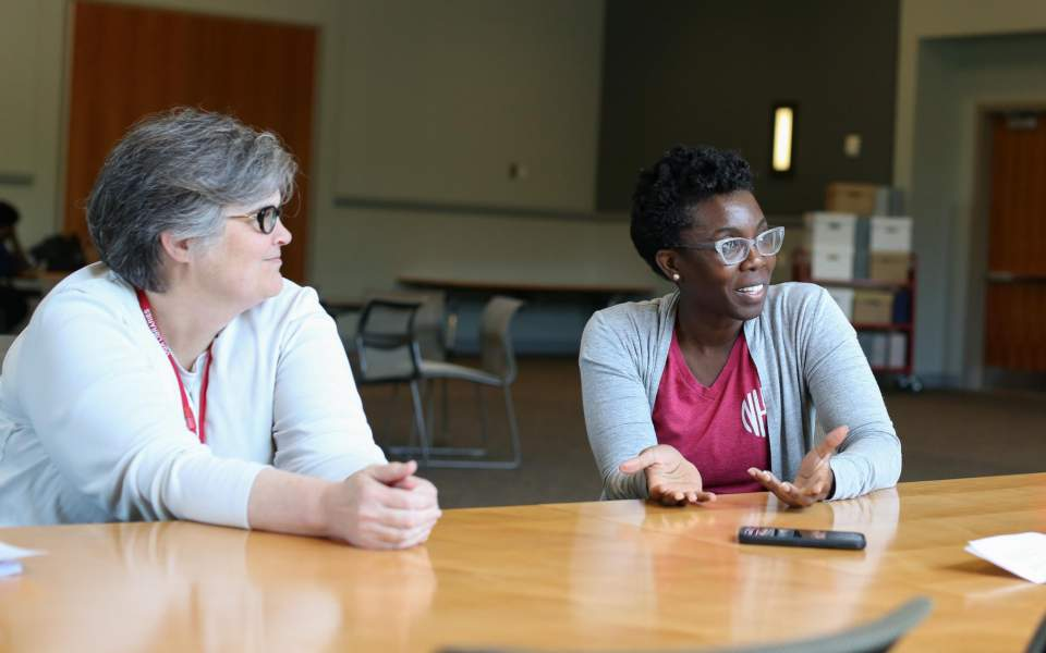 Jill Severn, Russell Library Archivist, red lanyard, and Dr. Amma Y. Ghartey-Tagoe Kootin. Image by Shannah Montgomery