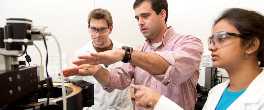 Faculty and Chemistry Graduate Students working in Laboratory|Chemistry Ph.D. student Evan White, left to right, talks with professor Jason Locklin and fellow Chemistry Ph.D. student Anandi Roy about an experiment on a m...