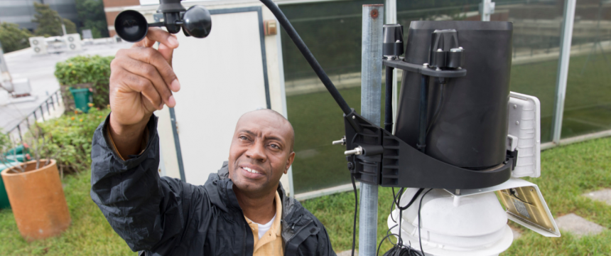 Professor Marshall Shepherd checks a weather station on top of the roof of the Geography Building.
