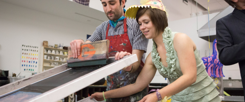Lamar Dodd School of Art Open House|l-r: Michael Levine, a 3rd year MFA printmaking major from Glastonbury Connecticut|and Jessica Machacek, a 2nd year MFA printmaking major from Omaha, NE pull silk screen print onto