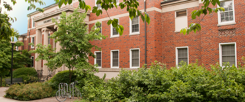Edged with shrubbery and trees, and with a bike rack at its columned entrance, Gilbert Hall was once the campus hospital.