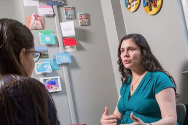 Graduate student Lunara Goncalves interacts with professor Cecilia Rodrigues inside an office.