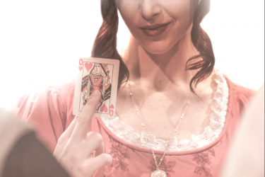 promo photo of woman holding playing card