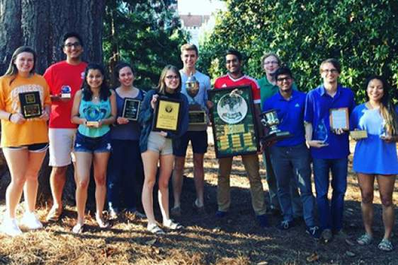 students with plaques, trophies