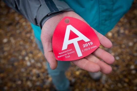photo of person holding a red baggage tag