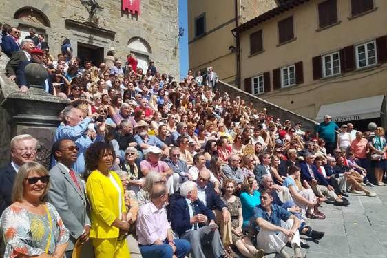 photo of a large group seated on sunny steps of a medieval palace.