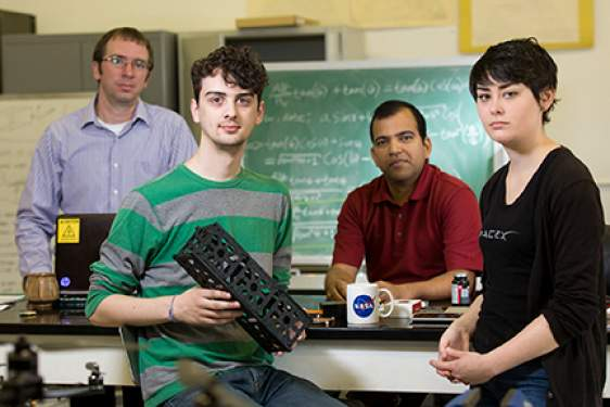 four people in a lab, with model