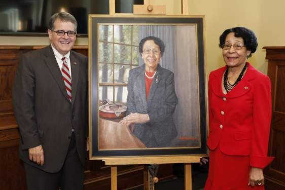 photo of two people with a painted portrait