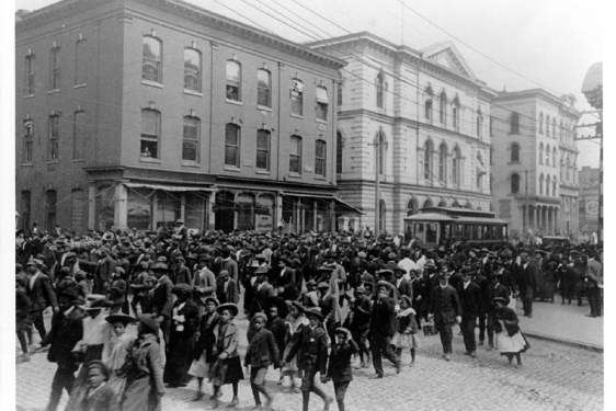 black and white historical photo of people marching on a city street