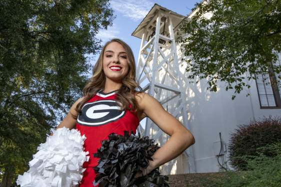 photo of cheerleader in front of the chapel bell