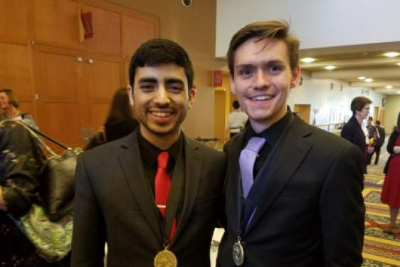 two men in a lobby with medals