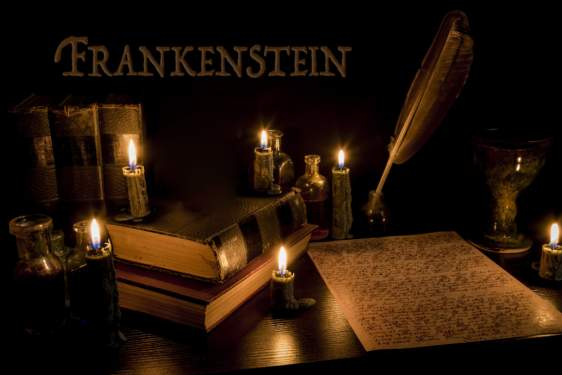 graphic with Frankenstein word, quill pen and paper, candles