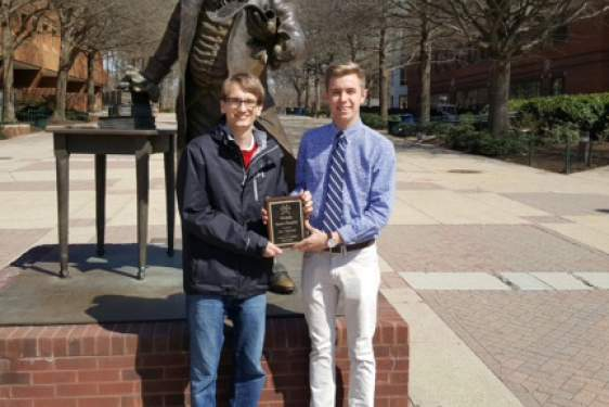 two students with plaque in front of statue