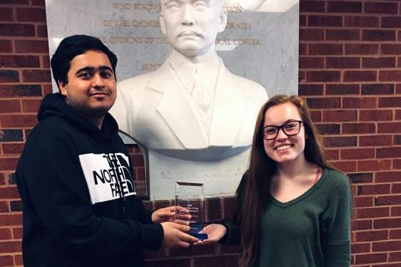 photo of two people with award and bust statue