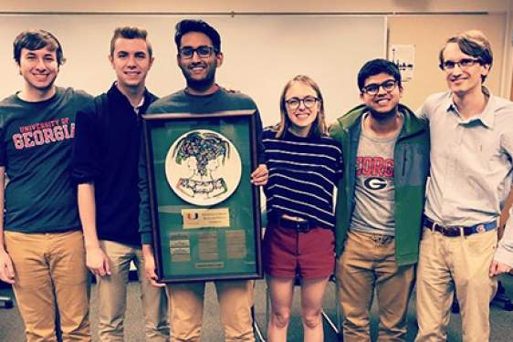 photo of five students with plaque