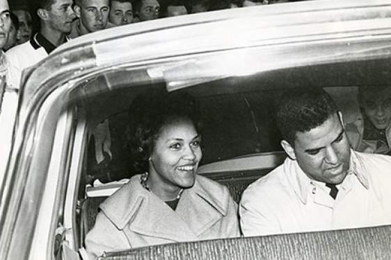 b/w photo of two people in a car, from outside