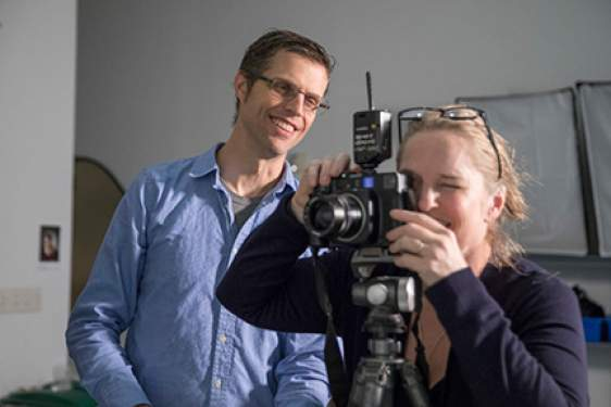 photo of man and student with camera