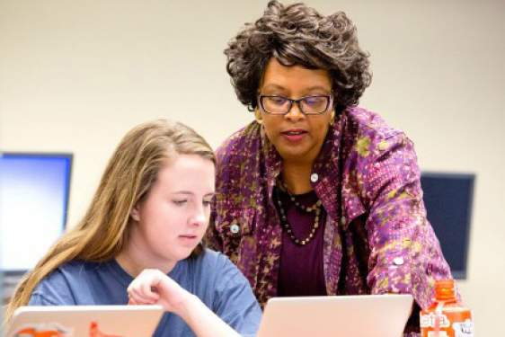 professor with student on computer