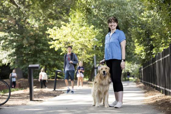 outdoor photo of woman with service dog on sidewalk and other pedestrians.