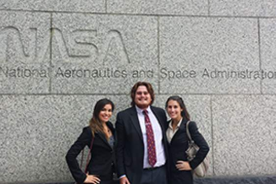 three students in front of NASA sign