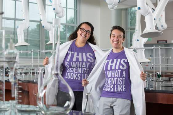 photo of women in lab coats and t-shirt in a lab