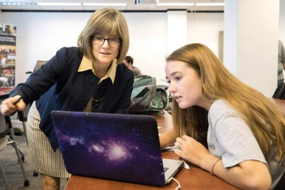 photo of two women with a computer