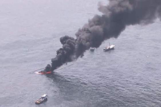 aerial photo of black smoke rising from the ocean water