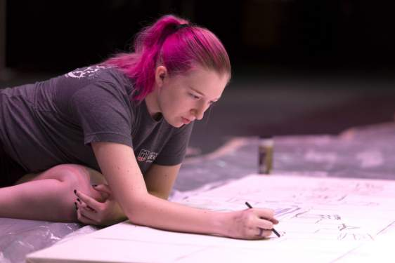 photo of woman leaning over a large drawing surface with pencils